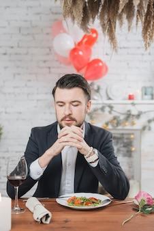 Hombre solitario adulto en mesa con cena romántica