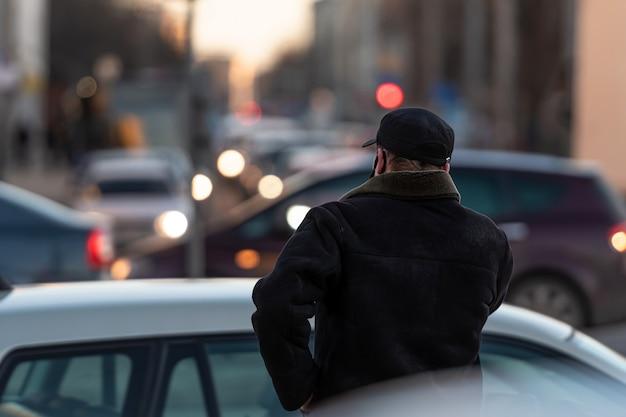 Un hombre solitario por detrás en una calle muy transitada con semáforos de la ciudad por la noche en la pared