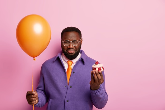 Hombre solitario disgustado molesto para celebrar el cumpleaños solo, se para con el globo y el pastel, tiene mal humor debido a las vacaciones estropeadas, viste un traje morado