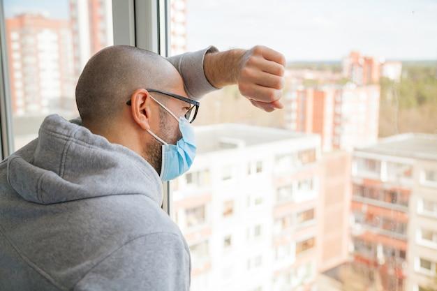 Hombre solitario en máscara médica mirando por la ventana