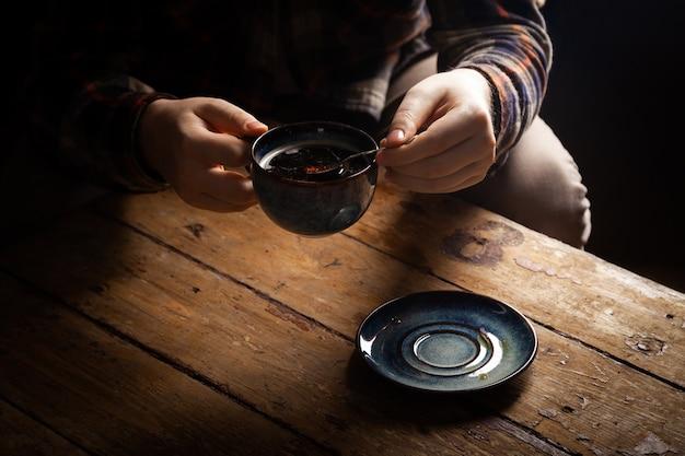 Hombre solitario con una taza de café americano negro en la mano