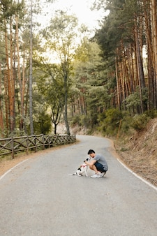 Hombre solo besando, abrazando y acariciando a su familiar perro labrador blanco y negro en la carretera en el bosque de pinos bajo la luz del sol de la tarde