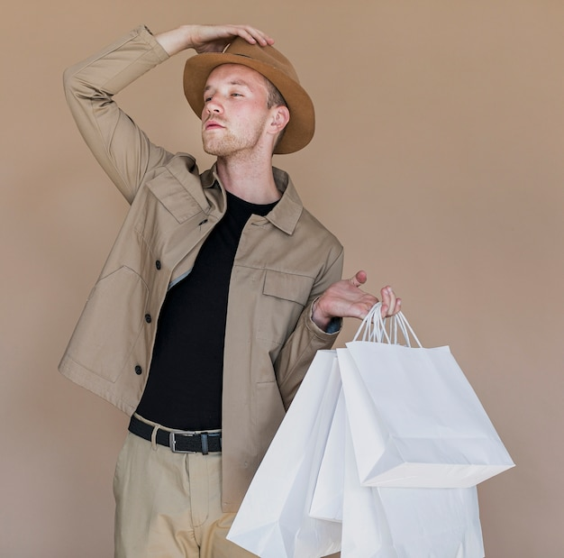 Hombre con sombrero y bolsas de compras sobre fondo marrón