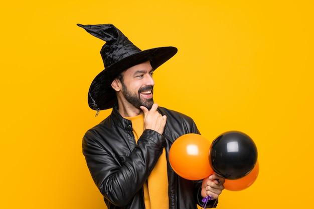 Hombre con sombrero de bruja sosteniendo globos de aire negro y naranja para la fiesta de halloween mirando hacia un lado