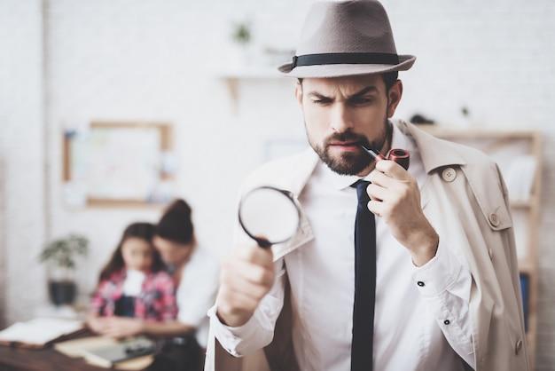 El hombre en sombrero y la capa está presentando con la lupa.