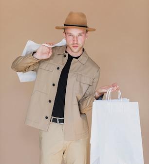 Hombre con sombrero marrón sosteniendo las bolsas de la compra.