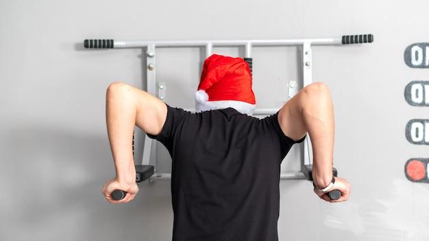 Un hombre con sombrero de navidad en las barras asimétricas en un gimnasio. vista trasera