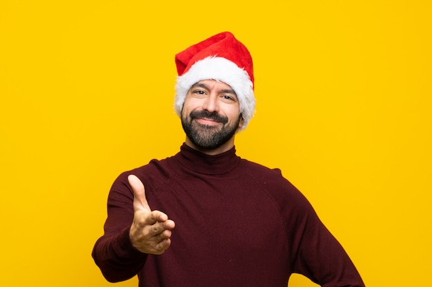 Hombre con sombrero de navidad estrechándole la mano para cerrar un buen trato