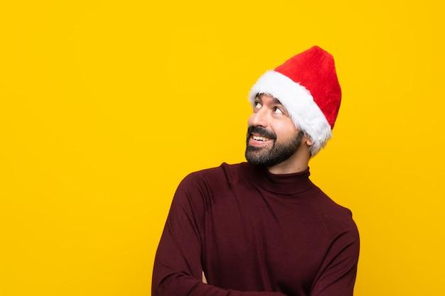 Hombre con sombrero de navidad sobre fondo amarillo aislado mirando hacia arriba mientras sonríe
