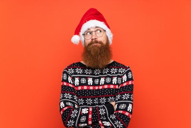 Hombre con sombrero de navidad sobre fondo rojo aislado