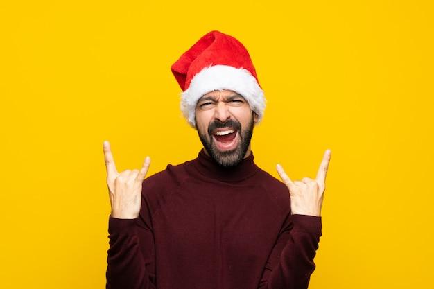 Hombre con sombrero de navidad sobre pared amarilla aislada haciendo gesto de rock