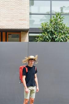 Hombre con sombrero de paja en la cabeza con mochila de equipaje