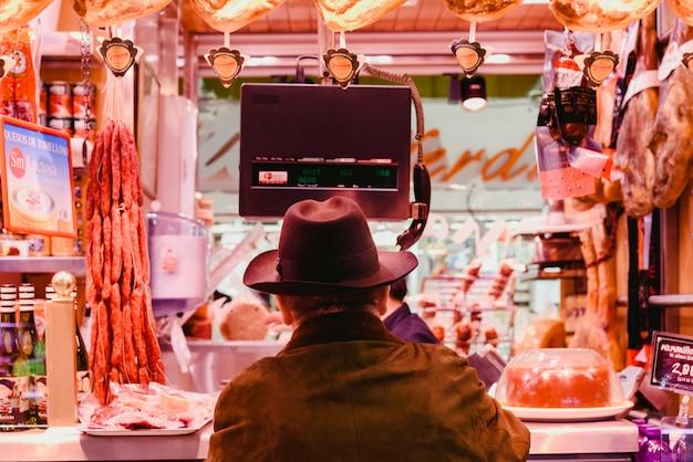 Hombre con el sombrero que compra la salchicha en una carnicería.