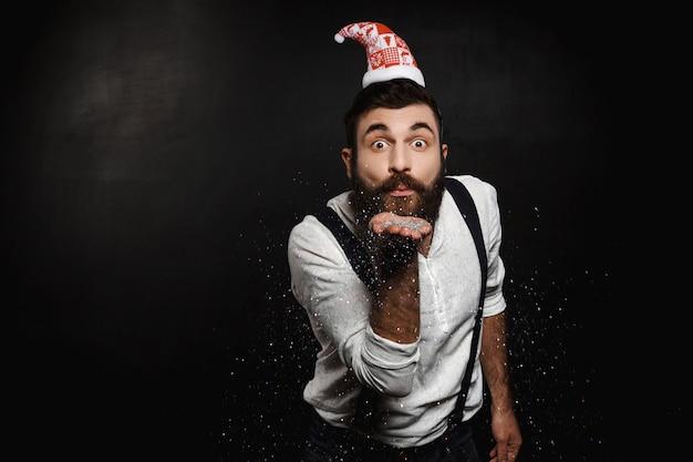Hombre con sombrero de santa claus soplando brillo plateado sobre negro.