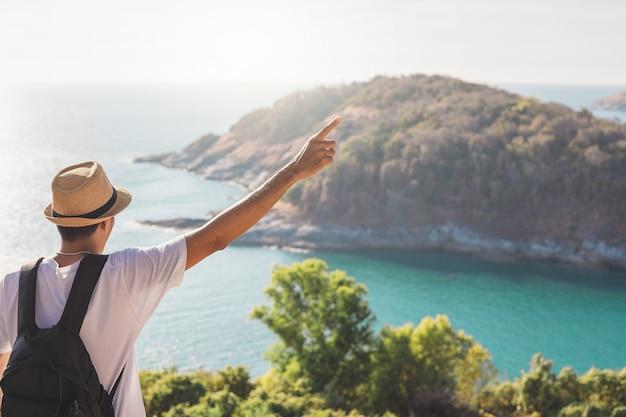 Hombre con sombrero tiene su mano feliz. hombre asiático turista mire las montañas y el mar antes del atardecer. para actividades estilo de vida al aire libre libertad o viajes turismo inspiración mochilero turista a covid 19