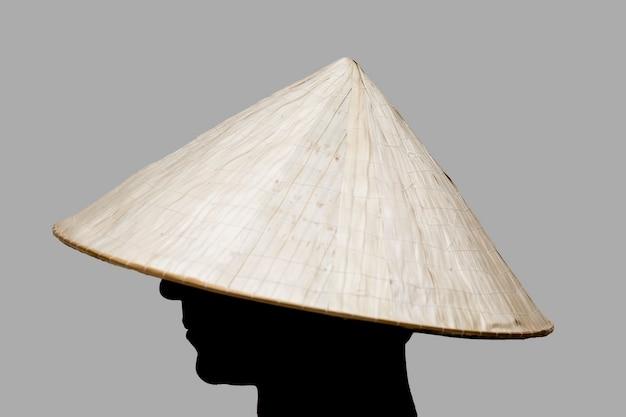Hombre con sombrero tradicional de asia hecho de mimbre.