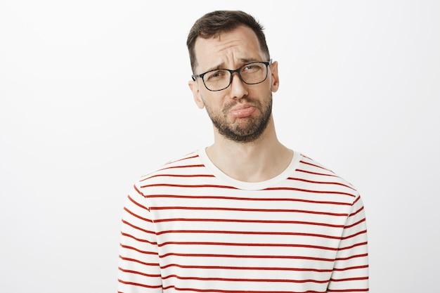 Hombre sombrío con barba con gafas, haciendo pucheros y llorando, quejándose con un amigo sobre su novio que se olvidó del aniversario.