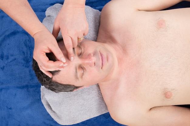 Hombre sometido a tratamiento de acupuntura con agujas finas insertadas en la piel de su frente