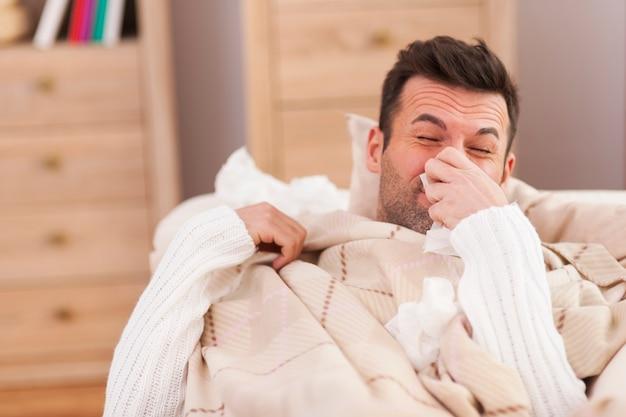 Hombre sonándose la nariz en la cama