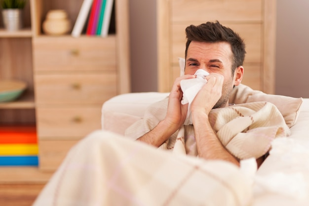 Hombre sonándose la nariz mientras está acostado enfermo en la cama