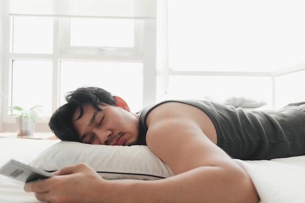Hombre soñoliento está usando el teléfono inteligente mientras está acostado en la cama.