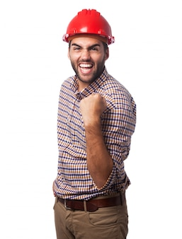 Hombre sonriendo con un casco rojo y un puño levantado