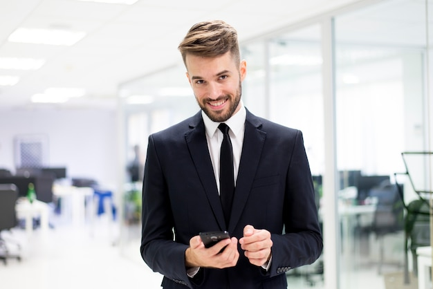 Hombre sonriendo elegante con un teléfono inteligente