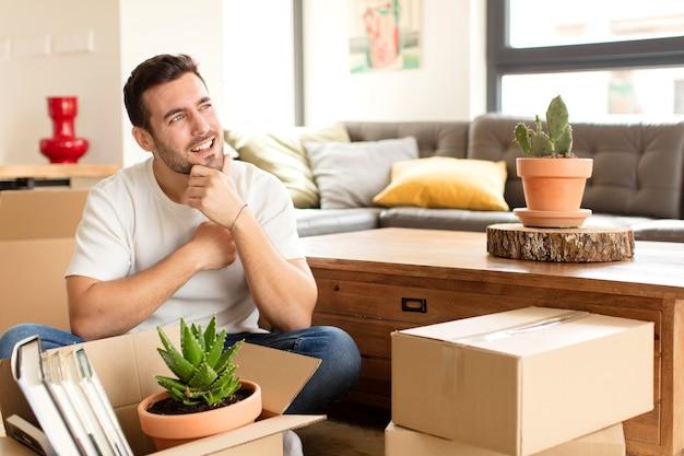 Hombre sonriendo con una expresión feliz y segura con la mano en la barbilla, preguntándose y el hombre mirando hacia un lado
