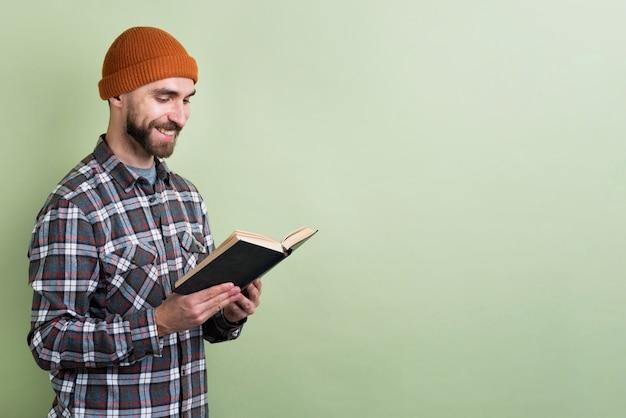 Hombre sonriendo mientras lee el libro