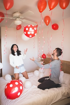 Hombre sonriendo mientras su novia mira la habitación llena de globos rojos