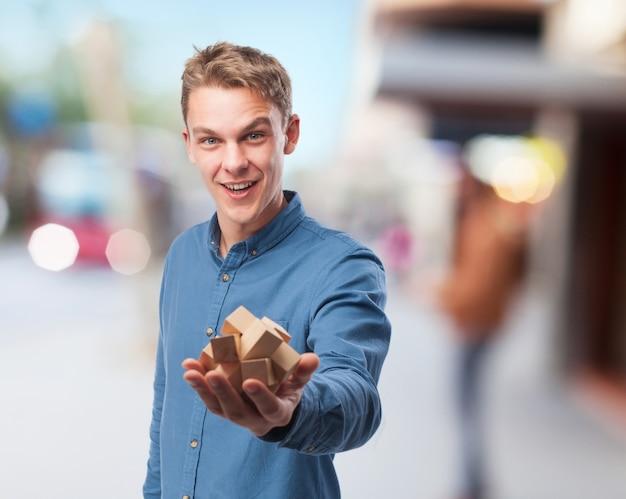 Hombre sonriendo mientras sujeta un juego de inteligencia de madera