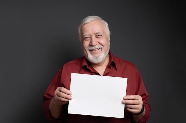 Hombre sonriente afable que sostiene una hoja de papel para la inscripción