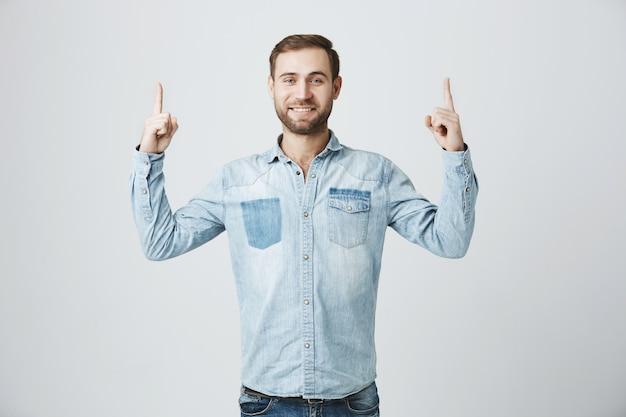 Hombre sonriente alegre apuntando los dedos hacia arriba, promover banner