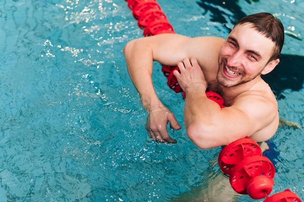 Hombre sonriente de alto ángulo tomando un respiro después de la práctica
