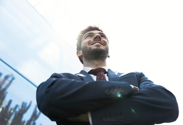 Hombre sonriente de ángulo bajo con los brazos cruzados