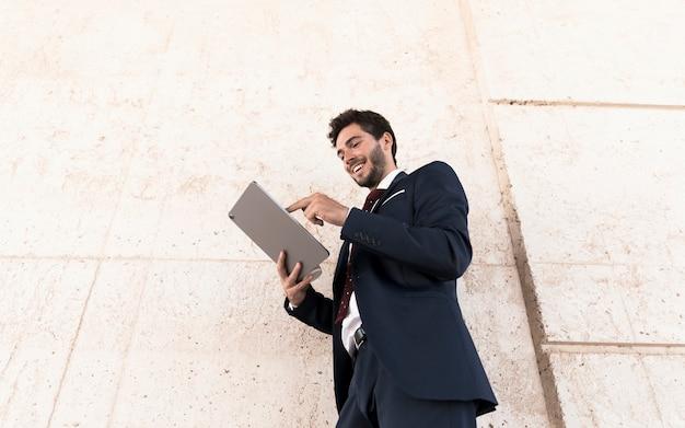 Hombre sonriente de ángulo bajo trabajando en tableta