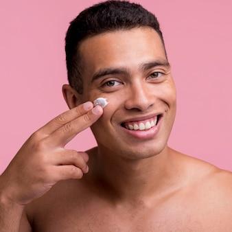 Hombre sonriente aplicando crema en el rostro