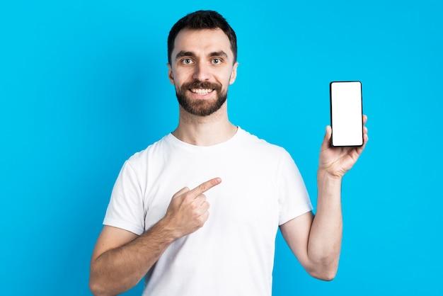Hombre sonriente apuntando al teléfono inteligente