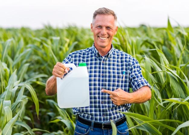 Hombre sonriente apuntando a un bote de insecticida