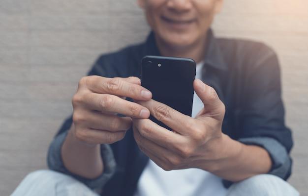 Hombre sonriente asiático videollamadas a través de teléfonos inteligentes móviles, de cerca