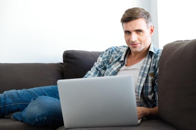 Hombre sonriente atractivo en camisa a cuadros y jeans sentado en el sofá y usando laptop