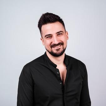 Hombre sonriente con barba en camisa negra