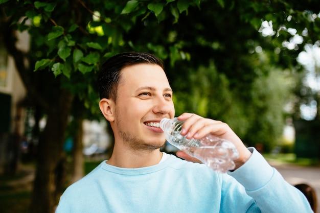 Hombre sonriente bebe agua de la botella en el fondo del árbol verde en día de verano