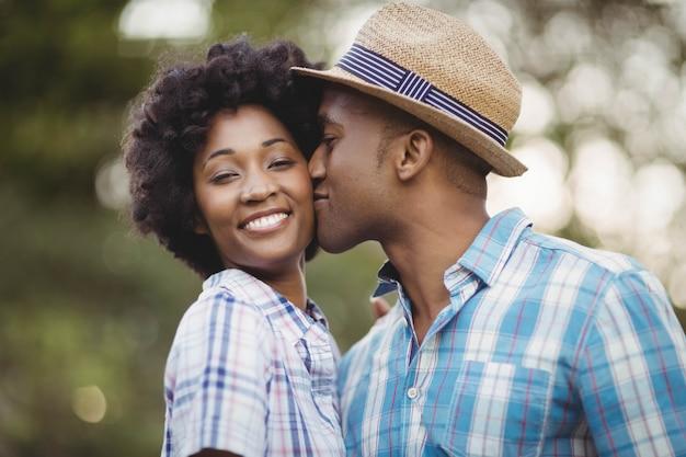 Hombre sonriente besando a su novia mejillas en el jardín