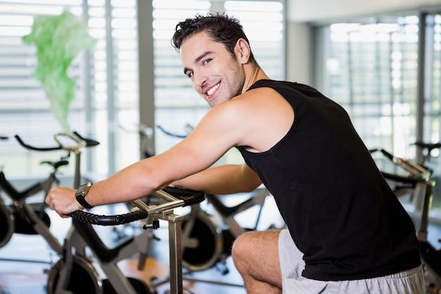 Hombre sonriente con bicicleta estática en el gimnasio