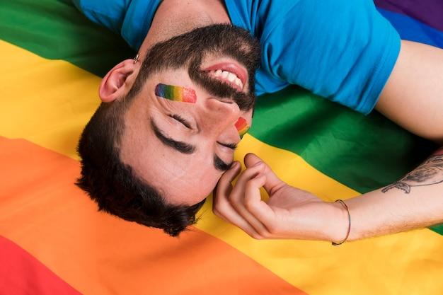 Hombre sonriente boca abajo que pone en la bandera lgbt multicolor