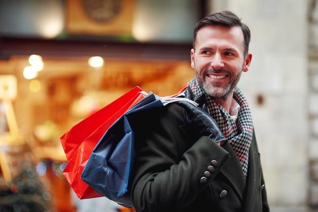 Hombre sonriente con bolsas de la compra.