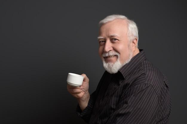 El hombre sonriente bondadoso que sostiene una taza y mira en el marco