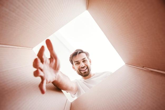 Hombre sonriente con el brazo estirado dentro de la parte inferior de la vista de caja