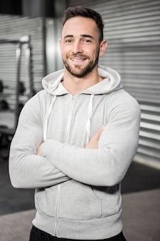 Hombre sonriente con los brazos cruzados en el gimnasio de crossfit